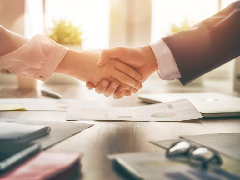Handshake over a desk with business papers on top.