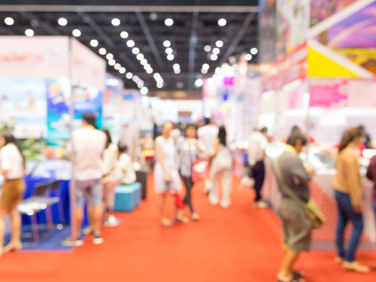 Blurred out photo of a tradeshow with attendees.