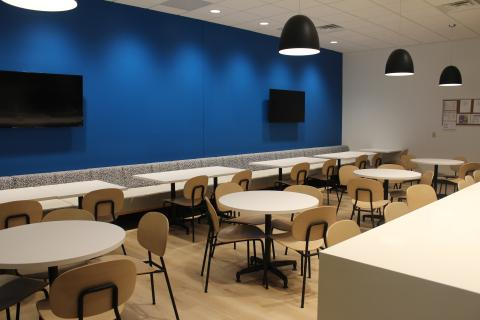 AIA Cafeteria with bright blue wall and modern tables and chairs.