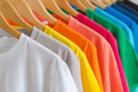 Bright colored t-shirts hanging on a clothing rack.
