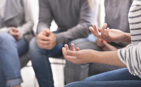 Group of people talking with focus on their hands.