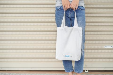 person holding white canvas bag